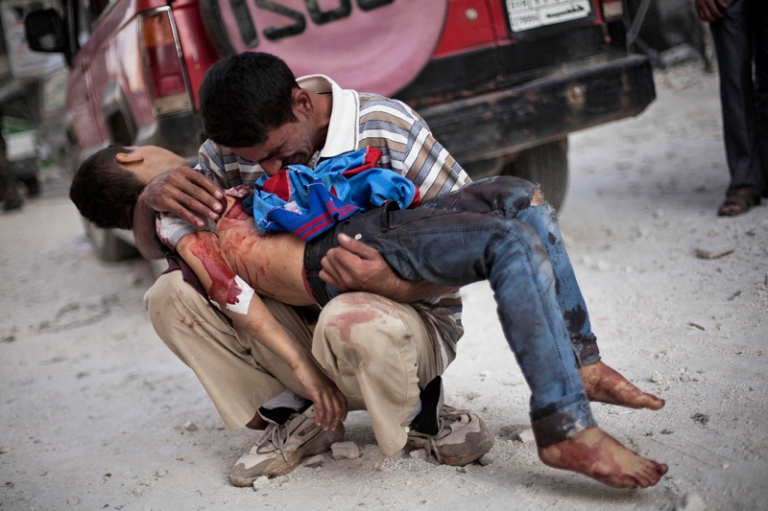 A Syrian man cries while holding the body of his son near Dar El Shifa hospital in Aleppo, Syria, Oct. 3, 2012. The boy was killed by the Syrian army
